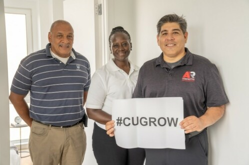 A woman and two men. One of the men is holding a sign that says #CUGrow.