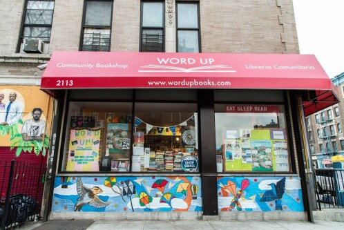 The red awning and display window of Word Up Community Bookstore.